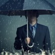 Businessman with an umbrella in the rain. — Stock Photo