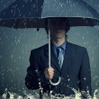 Stock Photo: Businessman with an umbrella in the rain.