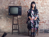 Woman and an old television in front of a brick wall. — Stock Photo
