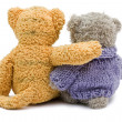 Stock Photo: Back view of two Teddy bears hugging each other over white