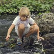 Boy sitting on the stones near the river — Stock Photo