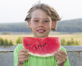 Beautiful boy eats a piece of watermelon — Stock Photo