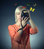 Woman with camera and butterflies — Stock Photo