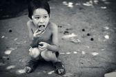 Solitário garoto faminto come sentado no chão — Fotografia Stock