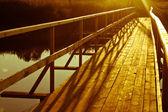 Wooden bridge over the river — Stock Photo