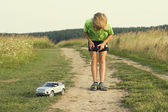 Child playing with a remote controlled toy car — Stock Photo