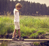 Boy on a wooden bridge — Stock Photo