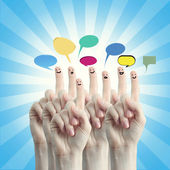 Finger smileys with social chat sign and speech bubbles — Stock Photo