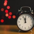 Alarm clock on a background of holiday lights. — Stock Photo #35928855