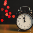Alarm clock on a background of holiday lights. — Stock Photo