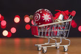 Christmas tree decoration red ball on the shopping trolley — Stock Photo