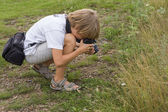 Boy making photographs of flowers — Stock Photo