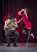 Man playing the trumpet, and a woman dancing — Stock Photo