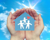 Hands holding house with happy family — Stock Photo