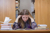 Student reading it in college library — Stockfoto