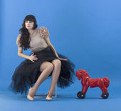 Woman with a toy horse. — Stock Photo