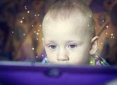 Niño mira una pantalla de ordenador. — Foto de Stock
