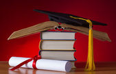Mortarboard and graduation scroll — Stock Photo