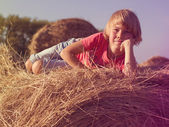 Boy lying on a haystack — Stock Photo
