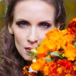 A beautiful brunette with flowers — Stock Photo #16890535