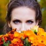 eine schöne Brünette mit Blumen — Stockfoto