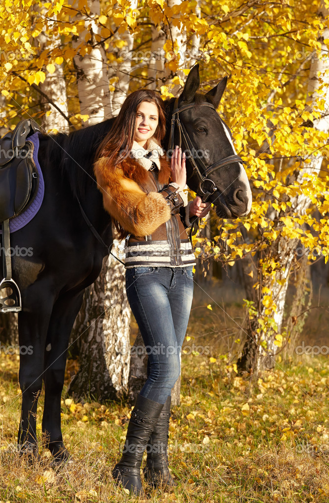 Portrait of a pretty young woman with a black horse riding autumn day — Stock Photo #18418773