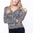 Beautiful blond woman in an animal print blouse — Stockfoto