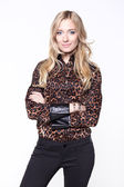 Beautiful blond woman in an brown animal print blouse — Stok fotoğraf