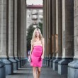 Blond fashion woman walking between columns — Stock Photo