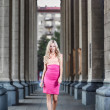 Blond fashion woman walking between columns — Stock Photo #34244291