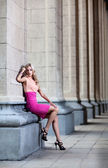 Female with pink dress against a column — Stock Photo