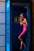 Young woman in telephone box — Photo