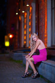 Young blond sits on parapet — Stock Photo