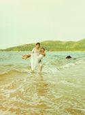 Instagram colorized vintage couple on beach portrait — Stock Photo