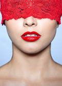 Oman with red lacy ribbon on eyes — Stock Photo