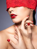 Woman with red lacy ribbon on eyes — Stock Photo