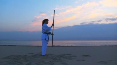 Young woman meditation on sunset beach — Stock Video