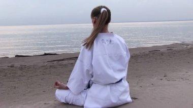 Jonge vrouw meditatie op zonsondergang strand — Stockvideo
