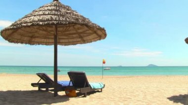 Tropical beach with straw umbrella and chairs — Stock Video