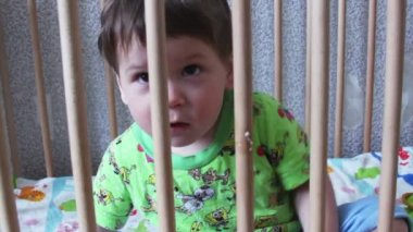 Boy in a crib — Stockvideo