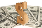 Wooden dollar sign with dollars — Stock Photo