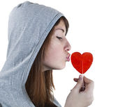 Candy red heart in the girl's lips — Stock Photo