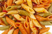 Penne rigate pasta with tomato sauce. background — Stock Photo