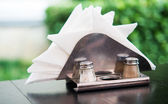 White napkins in holder on wooden table — Stock Photo