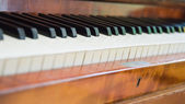 Closeup of antique piano keys and wood grain with sepia tone — Stock Photo