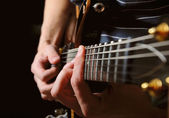 Guitarist hands playing guitar over black — Stock Photo