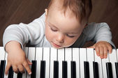 Baby play music on piano keyboard — Stock Photo
