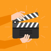 Two hands holding a cinema clapper in flat style — Stock Vector