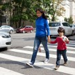 Woman with a child going on a pedestrian crossing in the city — Stok fotoğraf