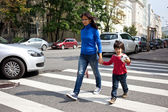 Woman with a child going on a pedestrian crossing in the city — Stock Photo